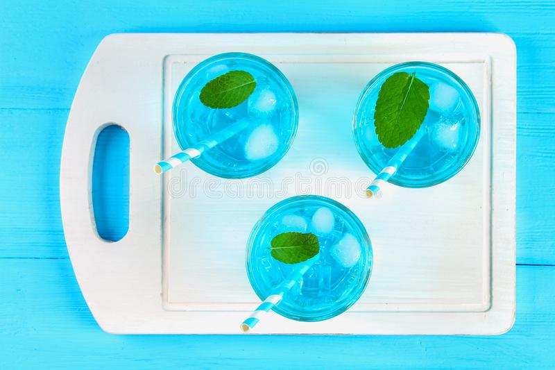 Cocktail azul com gelo e hortelã nos vidros em uma placa de madeira branca em uma tabela azul Vista superior imagem de stock royalty free