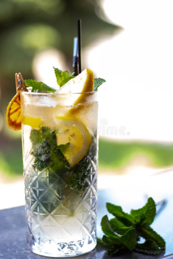 Cocktail based on lemonade, in a transparent large glass. In the inside of the black tubule, slices of lemon royalty free stock images