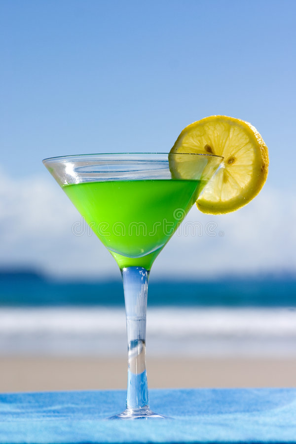 Cocktail on the beach. Close-up of Cocktail with Lime and dramatic sky stock images
