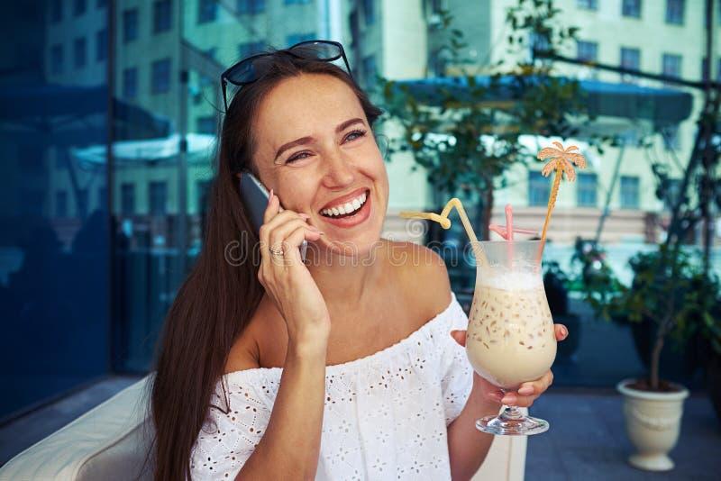Cocktail bebendo de sorriso da mulher no café exterior e na conversa sobre imagem de stock