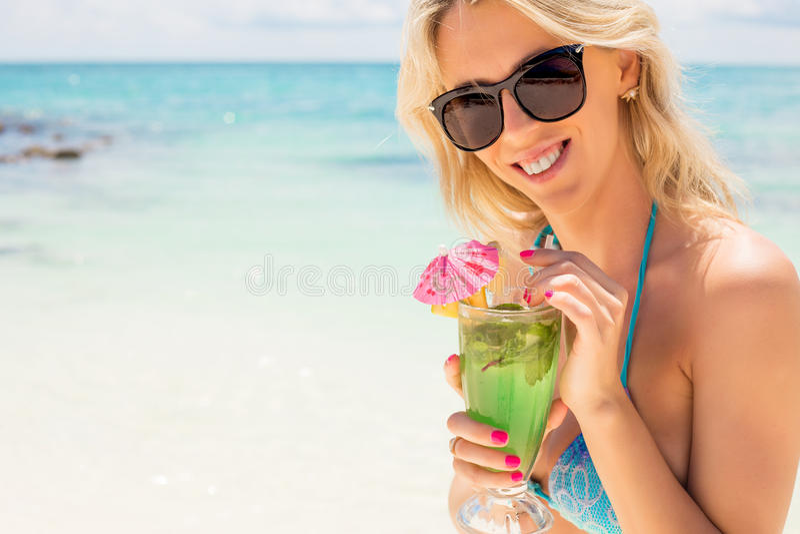 Cocktail bebendo do mojito da mulher feliz nova na praia fotografia de stock royalty free