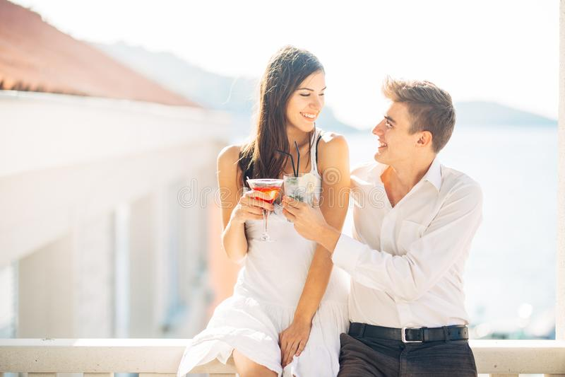 Cocktail bebendo dos pares atrativos, apreciando férias de verão Sorriso, atraído entre si Flertar e sedução imagem de stock