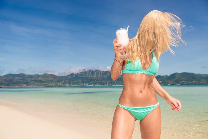 Cocktail bevente della donna sbalorditiva sulla spiaggia fotografia stock