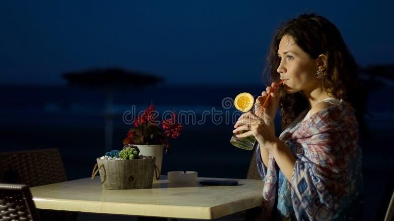 Cocktail bevente della giovane signora affascinante al ristorante della spiaggia vicino al suo hotel fotografia stock libera da diritti