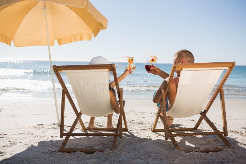 Cocktail beventi delle coppie felici mentre rilassandosi sul loro cha della piattaforma immagine stock