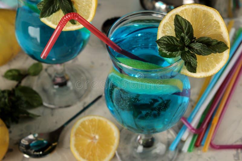 Cocktail blauwe lagune in een cocktailglas met citroen en munt op een bruine houten lijst in de bar stock afbeelding