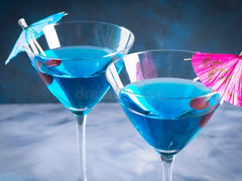 Cocktail bleu en verre de martini avec le parapluie photographie stock