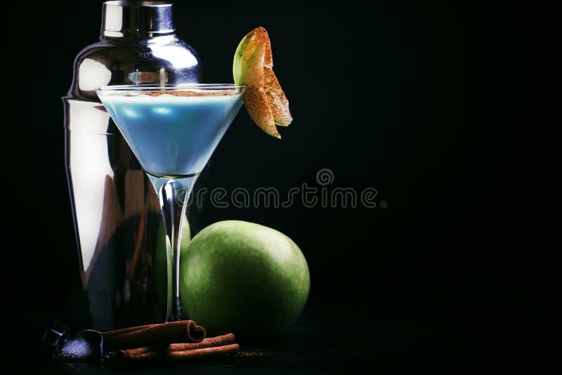Cocktail blu con liquore, crema e la mela verde, strumenti della barra su un fondo nero del contatore della barra, spazio della c immagine stock libera da diritti