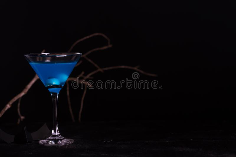 Cocktail blu di Halloween con i bulbi oculari artificiali in un liquido su un fondo nero immagine stock libera da diritti