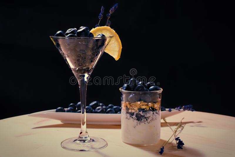 Cocktail with bluberriy in martini glass on wooden table. Coctail with bluberriy in martini glass on wooden table and black backgrouns stock photos