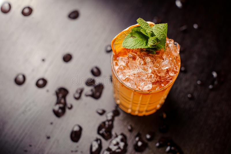 Cocktail brilhante com folhas de hortelã e uma fatia alaranjada fotos de stock