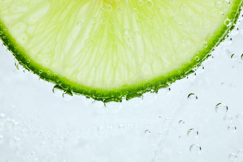 Cocktail close-up. Slice of fresh lime in cocktail stock images