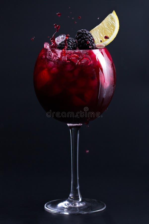 cocktail Cocktail rosso scuro con ghiaccio, le more e una fetta di limone Spruzzata fotografia stock