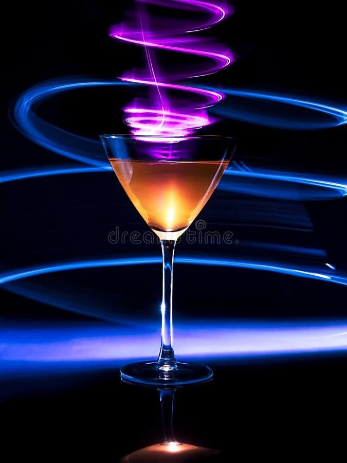 Cocktail coloré en verre avec des effets de la lumière sur le fond foncé photos libres de droits