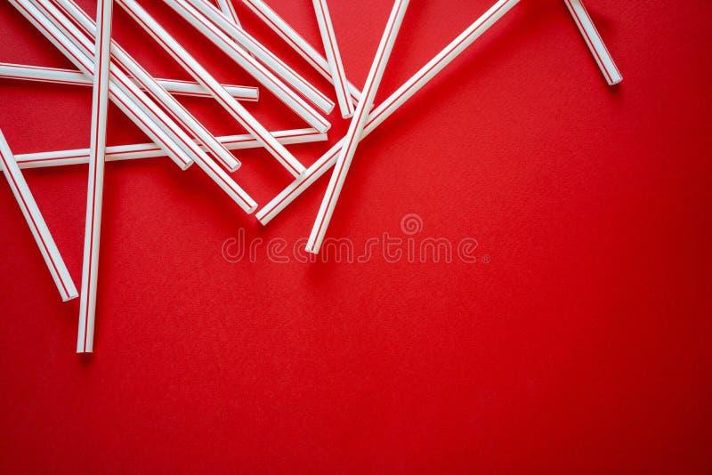 Cocktail color? de paille sur un fond rouge photo stock