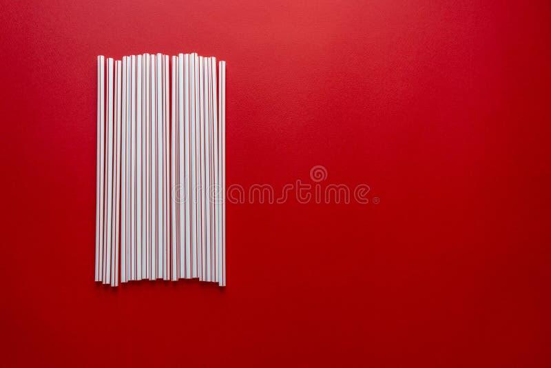 Cocktail color? de paille sur un fond rouge images stock