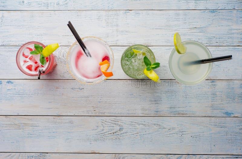 Cocktail coloridos Mojito, cocktail vermelho com gelo e cal, Margarita, cosmopolita no fim de madeira da tabela acima fotos de stock