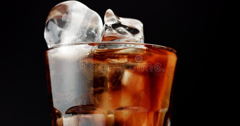 Cocktail com as fatias da cola e dos cais isoladas no preto fotos de stock royalty free