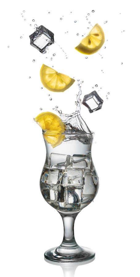 Cocktail com a fatia do gelo, do respingo e do limão isolada imagem de stock royalty free