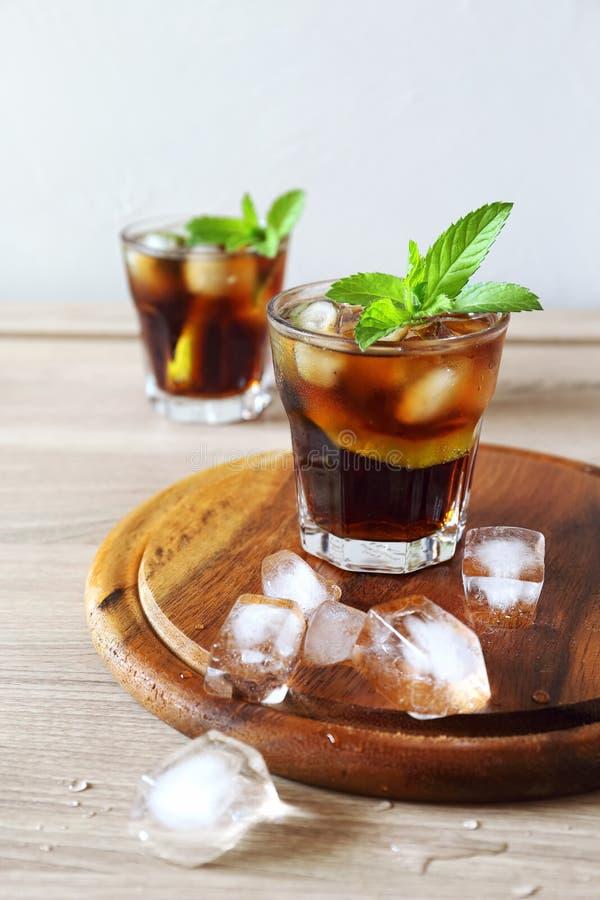 Cocktail com fatias da cola e dos cais fotografia de stock royalty free