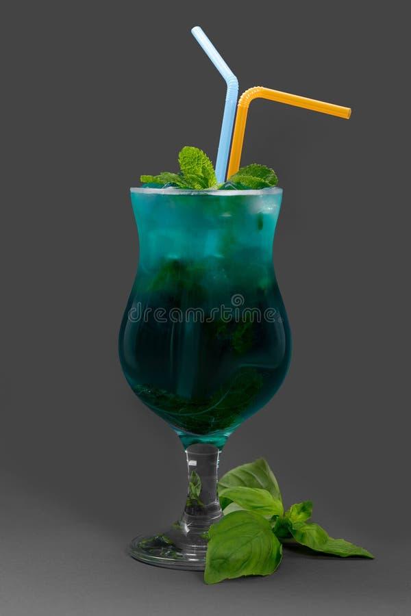Cocktail com hortelã e gelo no vidro azul Servido com tubos e manjericão no fundo cinzento fotos de stock