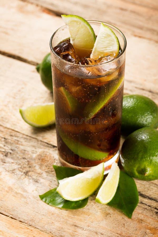 Cocktail com os cubos e o cal de gelo da cola fotografia de stock royalty free