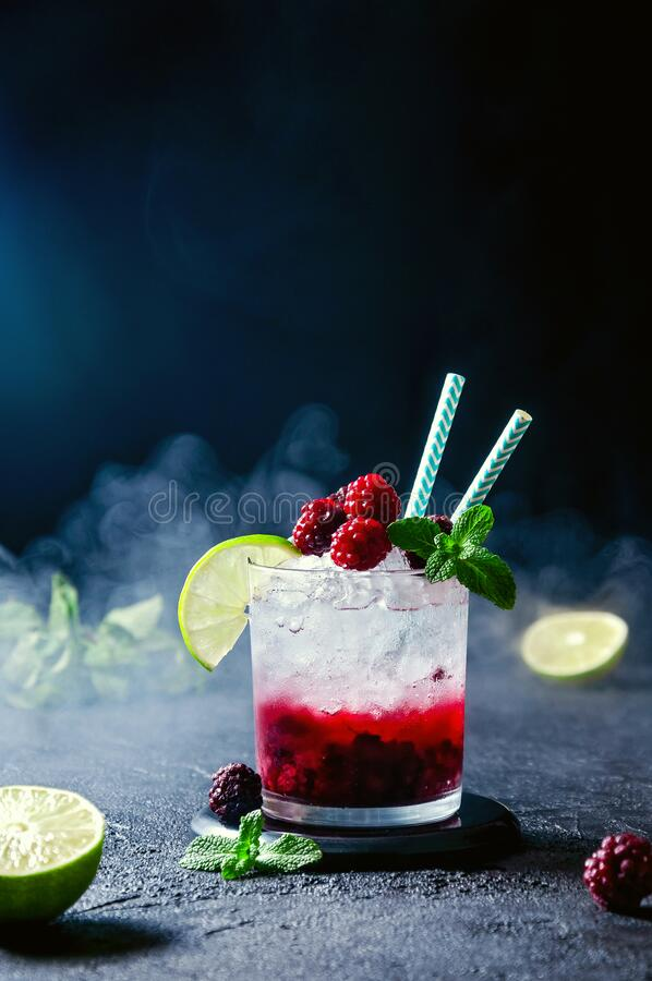 Cocktail com Rum ou Vodka, Soda, Raspberry e Blackberry Puree, Lime e Mint com Smok em Fundo Escuro fotos de stock