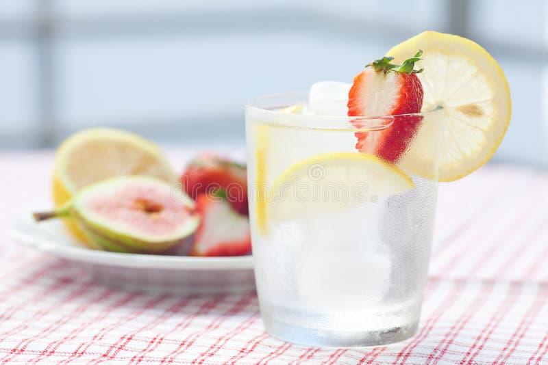 Cocktail con ghiaccio, il limone, il fico e le fragole fotografia stock