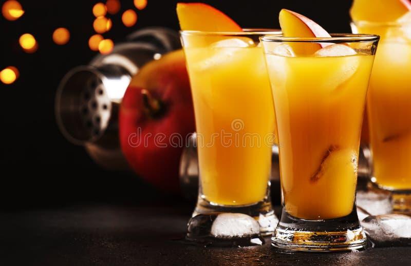 Cocktail con il succo del mango ed il liquore arancio, fondo scuro del contatore della barra, fuoco selettivo immagini stock libere da diritti