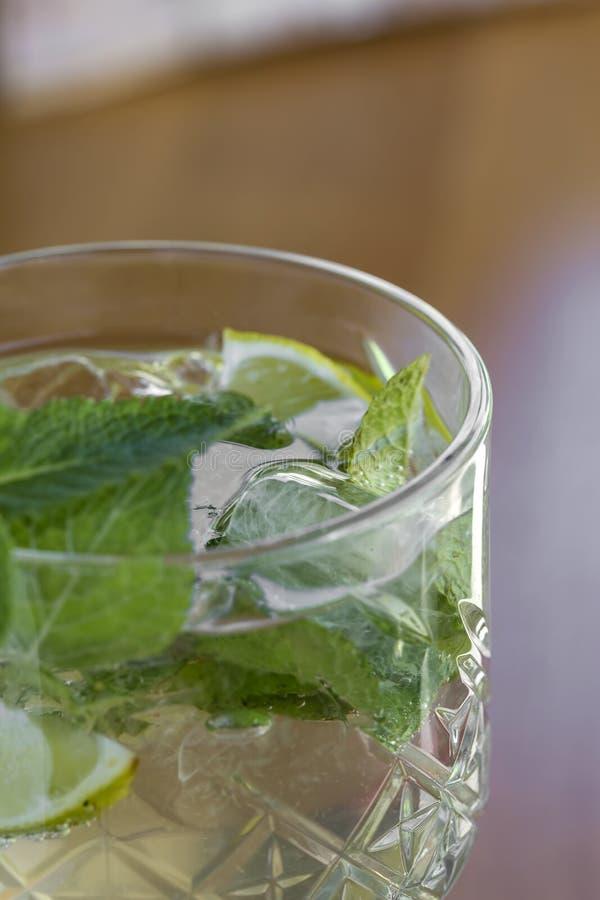Cocktail con vodka, la menta ed il limone in vetro sulla barra fotografie stock