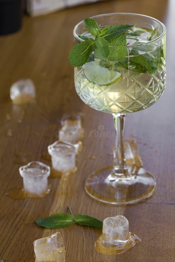 Cocktail con vodka, la menta ed il limone in vetro sulla barra con ghiaccio fotografia stock libera da diritti