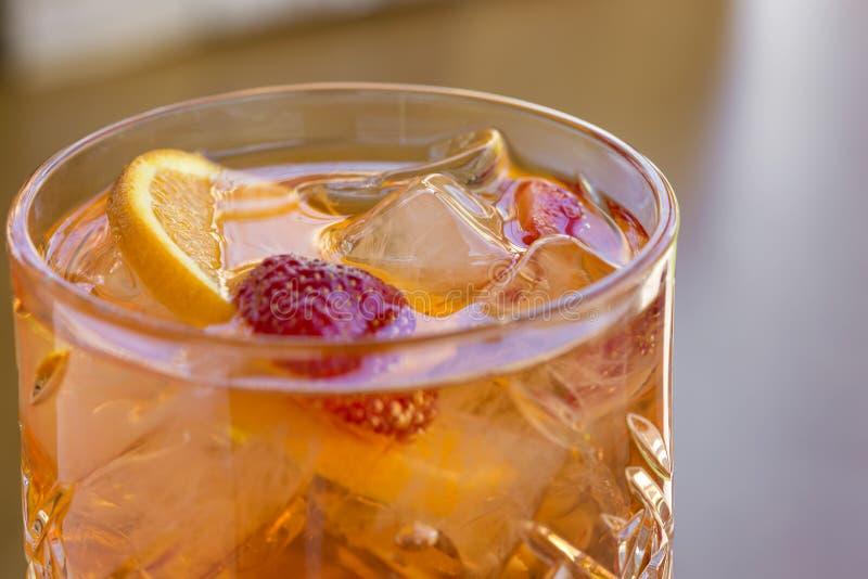 Cocktail con vodka, le fragole ed il limone in vetro sulla barra fotografie stock