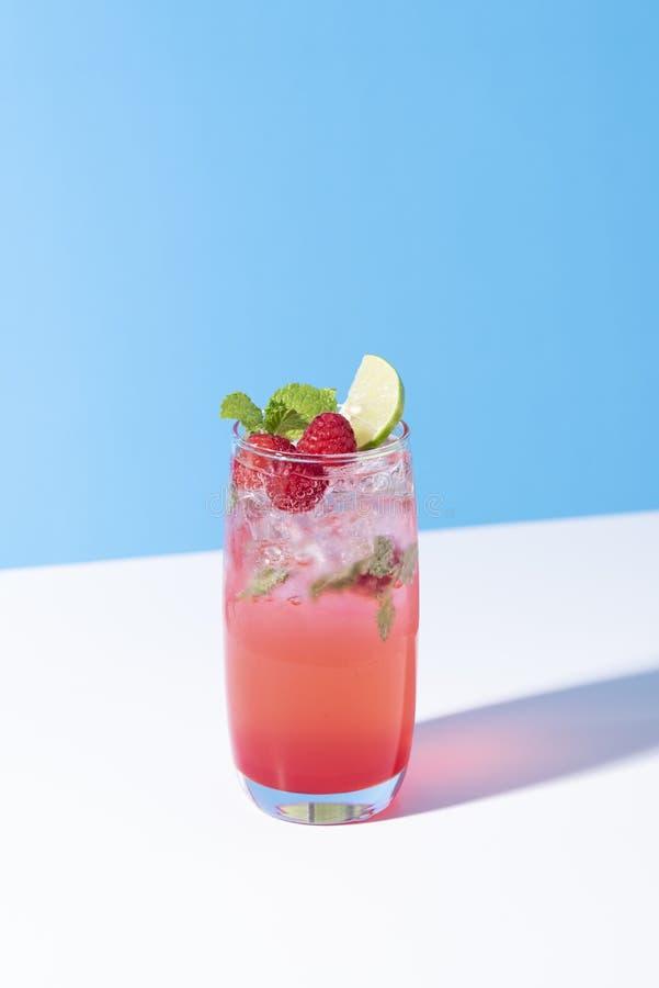 Cocktail congelado do perfurador da framboesa vermelha com cal no vidro no fundo da cor Bebida do ver?o imagem de stock