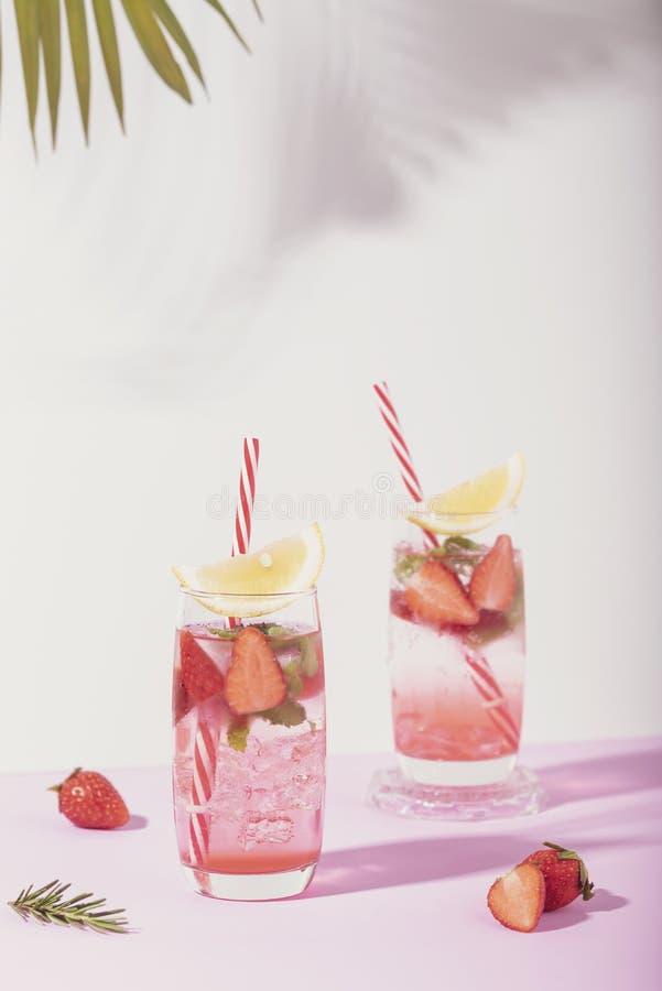 Cocktail congelado do perfurador da morango no vidro com o lim?o no fundo branco Bebida do ver?o imagem de stock