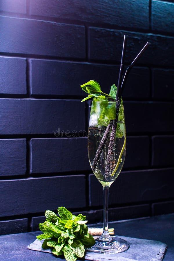 Cocktail contro il muro di mattoni nero fotografia stock
