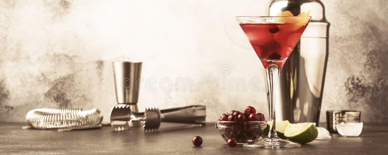 Cocktail cosmopolite avec la vodka, la liqueur, le jus de canneberge, la chaux, la glace et l'entrain orange, fond de compteur de photographie stock