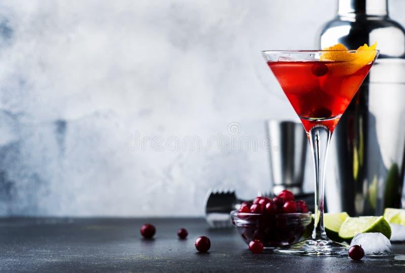 Cocktail cosmopolite avec la vodka, la liqueur, le jus de canneberge, la chaux, la glace et l'entrain orange, fond de compteur de photographie stock libre de droits