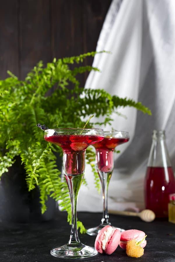 Cocktail cosmopolite ou de margarita garni avec macarons et baies sur un fond foncé avec une fleur verte photographie stock