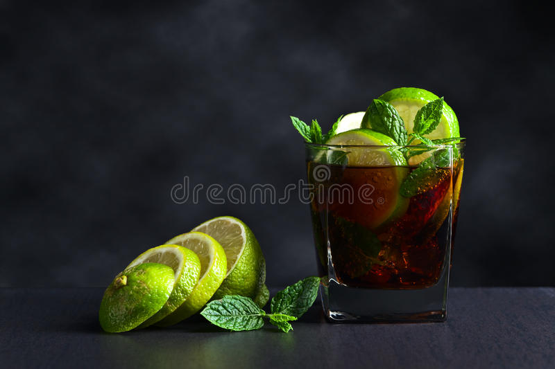 Cocktail Cuba libre with lime and peppermint leaves royalty free stock photography