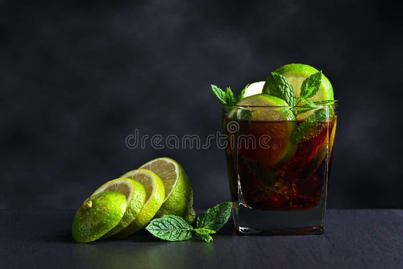 Cocktail Cuba libre met kalk en pepermuntbladeren royalty-vrije stock fotografie