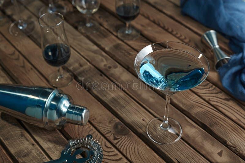 Cocktail dans un bleu en verre de martini sur une table en bois photographie stock