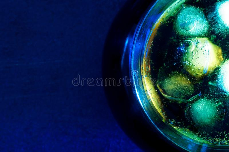 Cocktail of dark drink with ice on the bar of a nightclub. Blue light royalty free stock photos