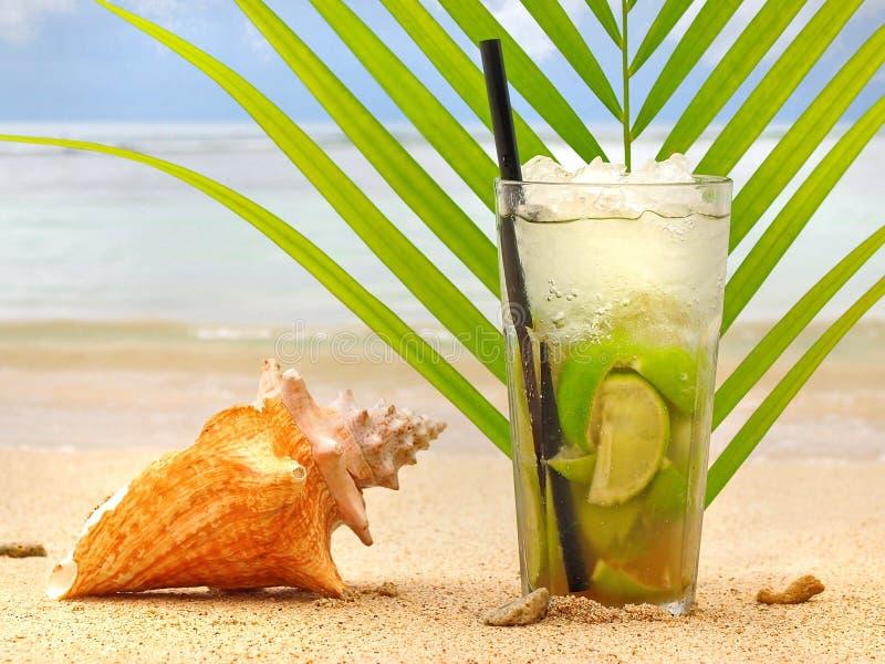 Cocktail de Caipirinha com a folha na praia imagens de stock royalty free