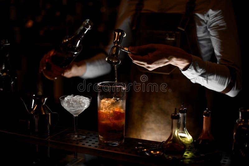 Cocktail de derramamento do álcool do barman usando o jigger com punho imagens de stock