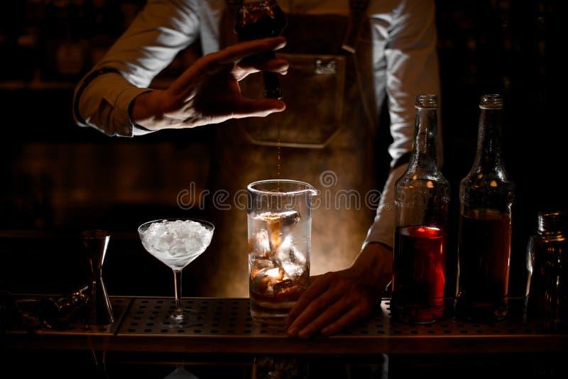 Cocktail de derramamento do barman do tubo de ensaio no vidro fotos de stock royalty free