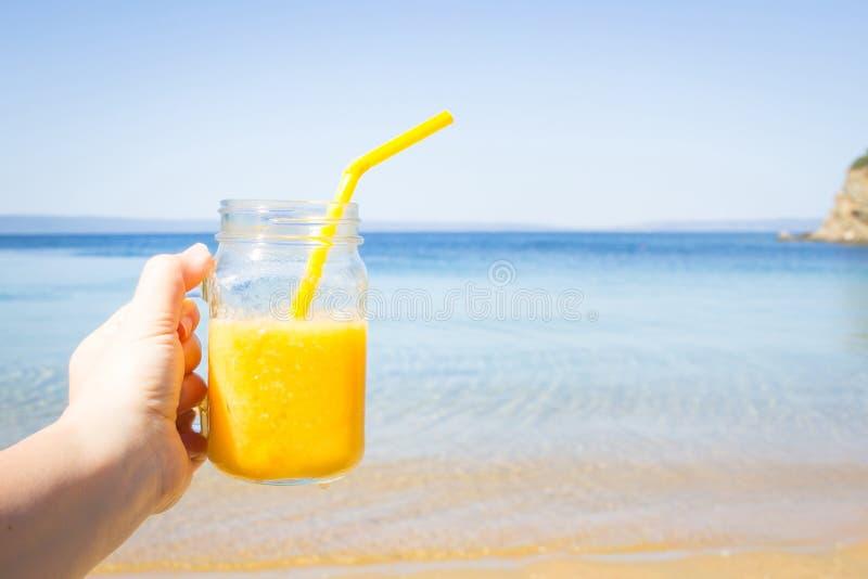 Cocktail de fruto na mão da mulher contra a praia tropical Rafrescamento do ver?o Conceito do curso e das f?rias Copie o espa?o imagem de stock