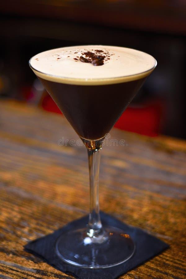 Cocktail de martini d'expresso avec des graines de café sur la barre photos stock