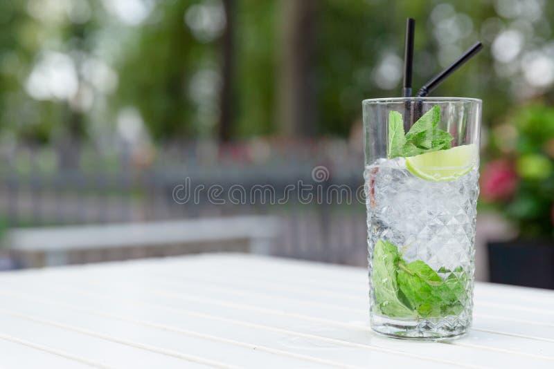 Cocktail de Mojito com cal e hortelã no vidro em uma tabela de madeira branca no restaurante exterior imagens de stock royalty free