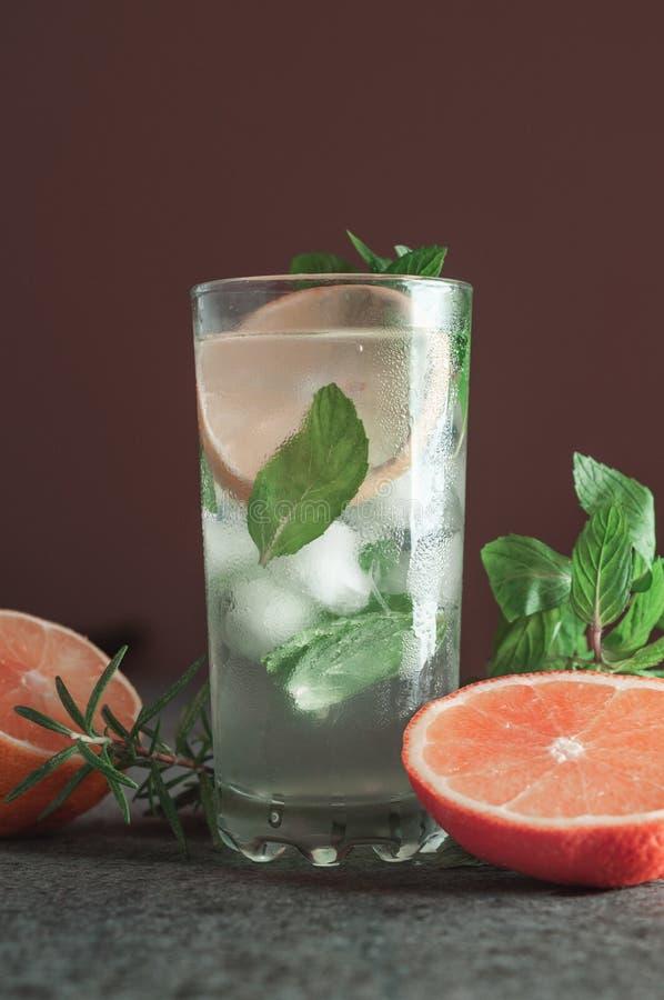 Cocktail de Mojito com cal e hortelã no vidro de highball em uma tabela de pedra cinzenta escura foto de stock