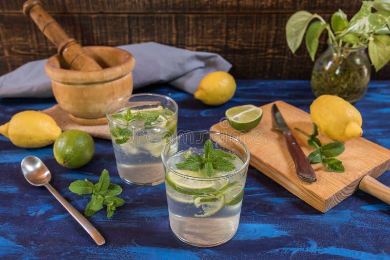 Cocktail de Mojito com seus ingredientes em uma tabela azul imagens de stock royalty free